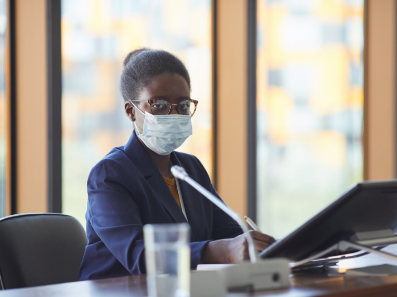 Stock photo of an African-American woman wearing a mask and seated at a table presenting from a laptop.