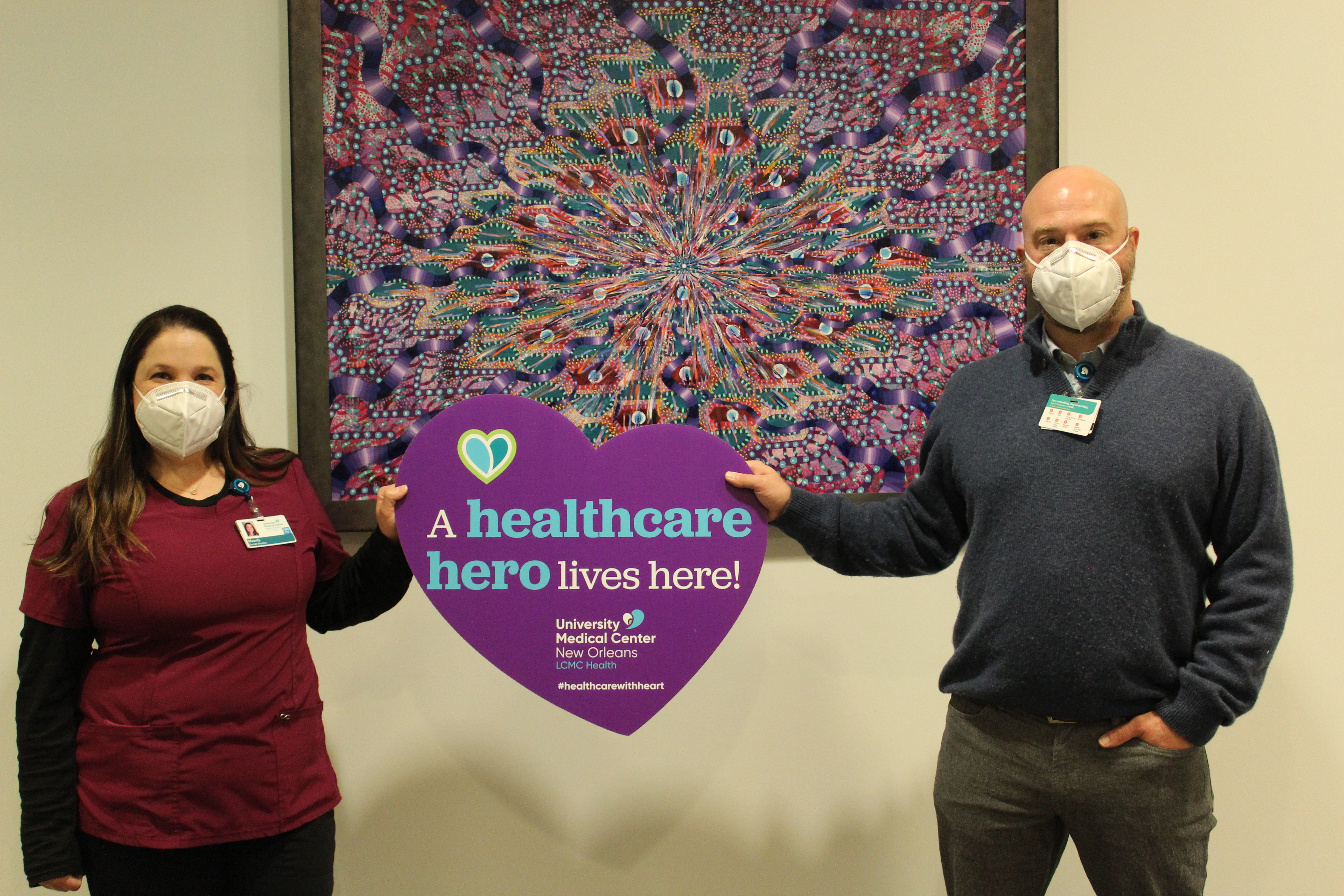 """A woman and a man wearing face coverings hold a sign shaped like a purple heart that says """"a healthcare hero lives here."""""""