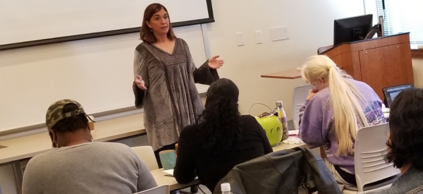 An adjunct professor gives a lecture in front of a class of students.